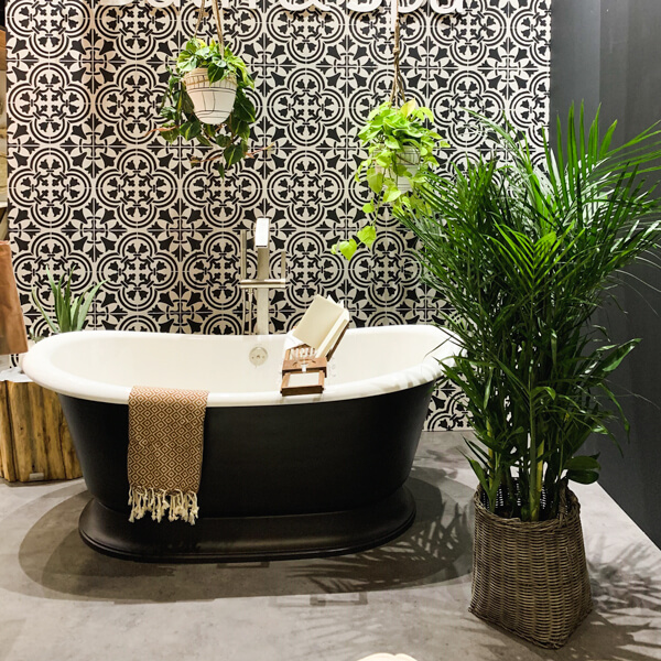 A modern free-standing tub with black and white geometric wallpaper at Benjamin Moore