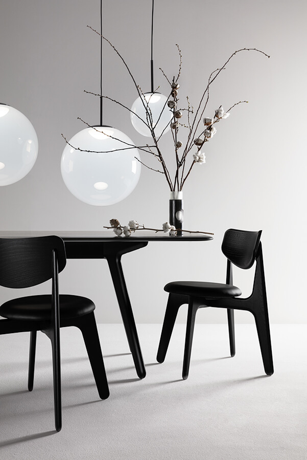Tom Dixon OPAL pendants with black SLAB dining chairs and table, and CARVED vase