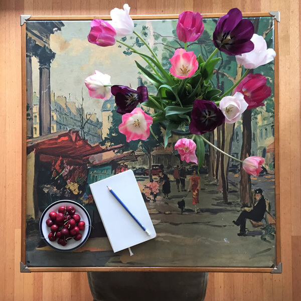 table with notebook, cherries, and tulips